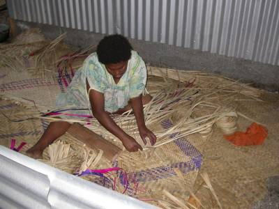 A villager at Epi Island weaves pandanus leaves into mats